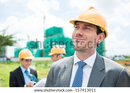 Image of a glad professional constructor on the foreground - stock photo