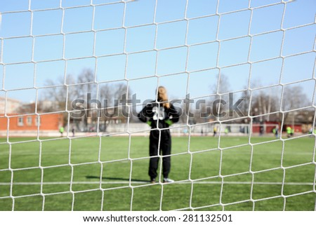 Image of a goalkeeper through the net. Women football - stock photo