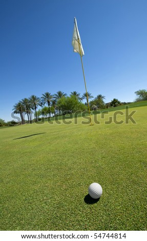 Image of a golf ball ongreen with flag - stock photo