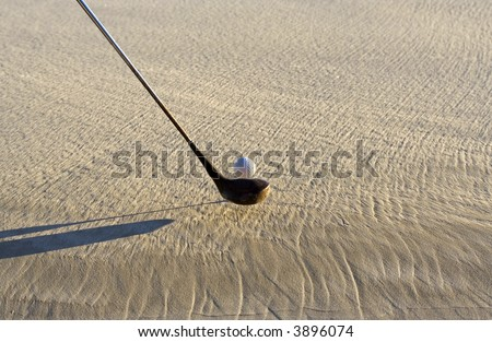 Image of a golf club and ball on sand - stock photo