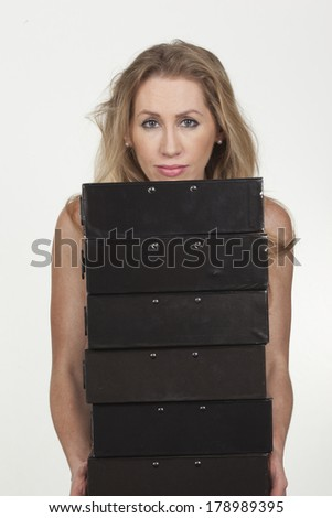 Image of a gorgeous female carrying many folders in her hands and looking straight, isolated on white. - stock photo