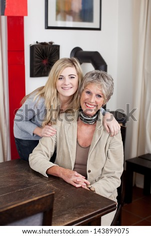 Image of a grandmother smiling and posing with her granddaughter. - stock photo