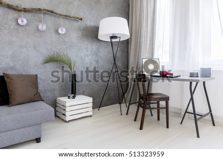 Image of a grey living room with cement wall effect, sofa, floor lamp, desk and chair