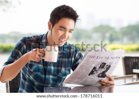 Image of a guy reading interesting news while drinking coffee at a cafe  - stock photo