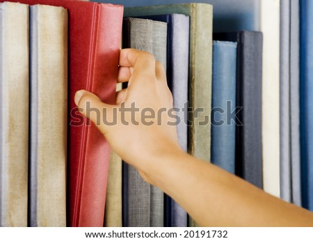 Image of a hand selecting a red book from a bookshelf - stock photo