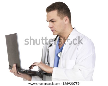 Image of a handsome young doctor working on a laptop while standing against white background
