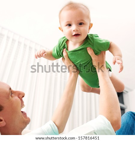 Image of a happy father playing with his little son on the foreground - stock photo