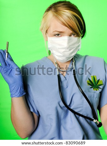 Image of a healthcare professional wearing surgical scrubs, stethoscope and mask presenting a marijuana joint on a chroma key background - stock photo