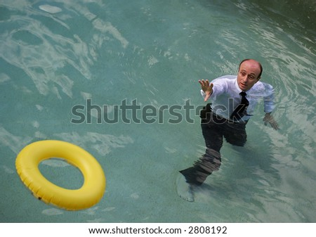 Image of a life saving ring being thrown to a business man. - stock photo