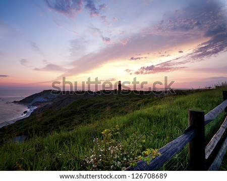 Image of a lighthouse during sunset with sky in the background. - stock photo