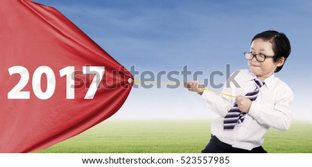 Image of a little businessman pulling banner with numbers 2017 in the meadow
