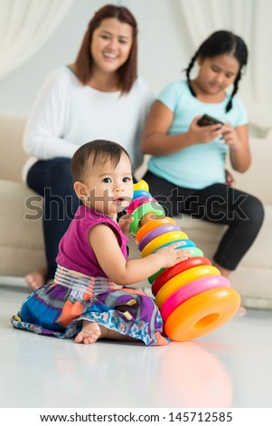 Image of a little cutie sitting on the floor and playing on the foreground