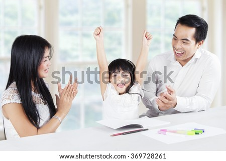 Image of a little girl finishing homework and get applause from her parents at home - stock photo