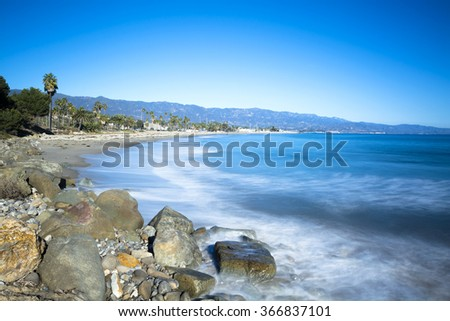 Image of a long exposure during a period where waves are approaching a sandy and rocky beach in Santa Barbara California - stock photo