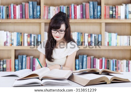Image of a lovely female student with long hair sitting in the library while learning and doing school task - stock photo