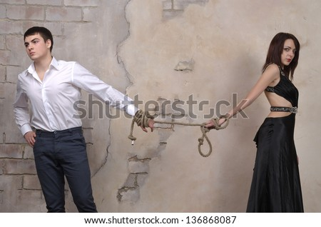 Image of a male and female model in a studio, their hands tied with a rope.