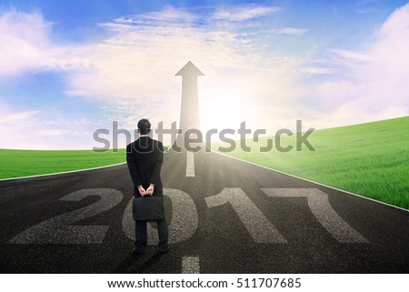 Image of a male worker standing on the highway with number 2017 and upward arrow
