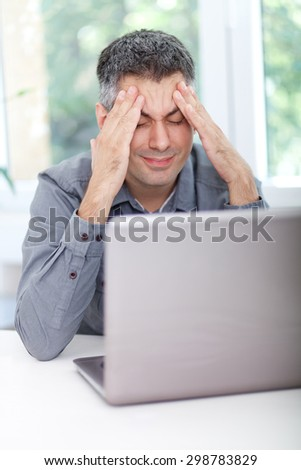 Image of a man at the desk, having headache - stock photo