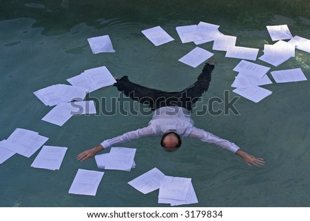 Image of a man drowning in paper work - stock photo