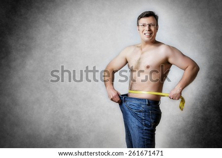 Image of a man in blue jeans with measuring tape who has lost body weight - stock photo