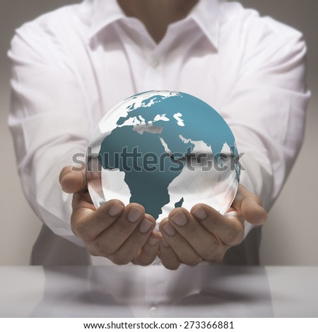 Image of a man in white shirt holding in its hands a glass earth. Earth concept for care and environmental protection or global business. - stock photo