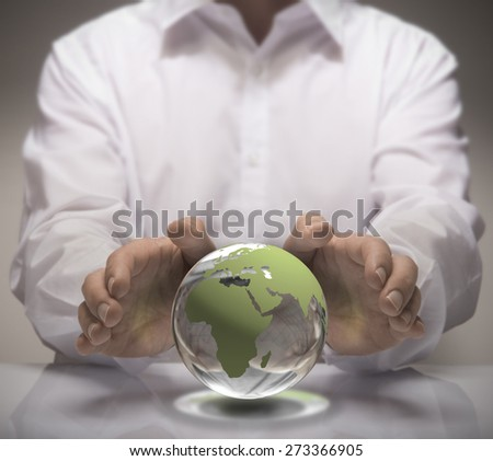 Image of a man in white shirt protect a glass earth with its hands. Earth concept for environmental protection or global business. - stock photo