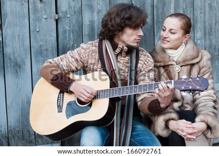 Image of a man playing the guitar and a woman sitting near him. - stock photo