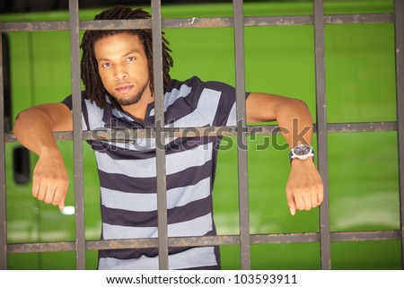 Image of a man posing behind bars on a green background