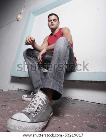 Image of a man sitting with shoe placed by the camera - stock photo