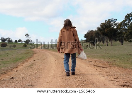 Image of a man walking along a country road - stock photo