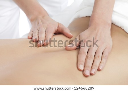 Image of a Masseuse giving a relaxing back massage at a spa - stock photo