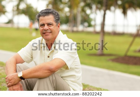 Image of a mature man sitting in the park - stock photo