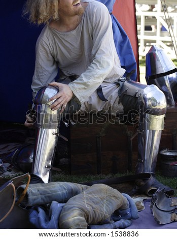 Image of a medieval soldier taking off his armour - stock photo