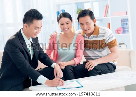Image of a middle-aged couple having financial consultation on the foreground - stock photo