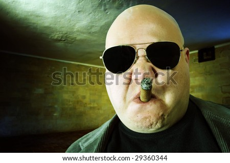 Image of a mobster, gangster, or boss in a dark factory setting. Harsh lighting, high-contrast and cross-processing for meaner look. - stock photo