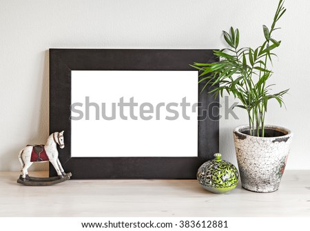 Image of a mockup scene with wooden frame, toy horse and plant pot.  - stock photo