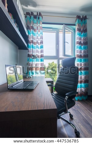 Image of a new study room with dark wooden desk, comfortable armchair, shelf and decorative window curtain