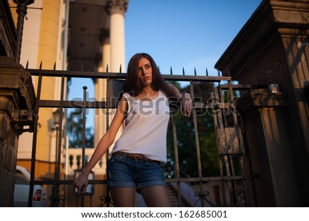 Image of a  pretty woman leaning on the fence.