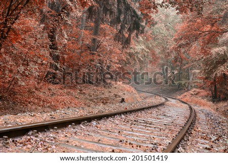 Image of a railway track with a sweeping curve edited in Autumn colours with a toned look - stock photo