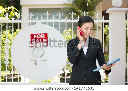 "Image of a realtor calling by phone near the ""for sale""?� house - stock photo"