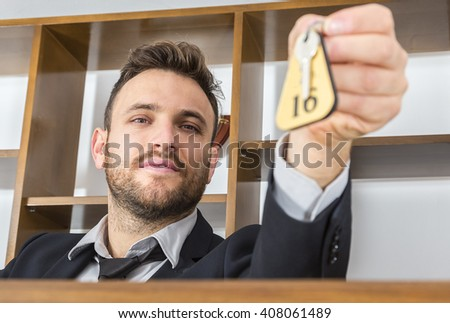 Image of a receptionnist at his desk giving the key to a client. Selective soft focus on the face.