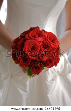 Image of a red rose bouquet in bride's hands - stock photo