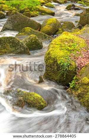 Image of a running river through moss covered rocks in Padley Gorge in the Peak District - stock photo