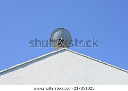 Image of a satellite dish sitting high at the apex of a white roof against a deep blue sky with room for copy space - stock photo