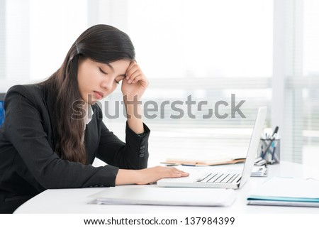 Image of a sleeping businesswoman at her workplace - stock photo