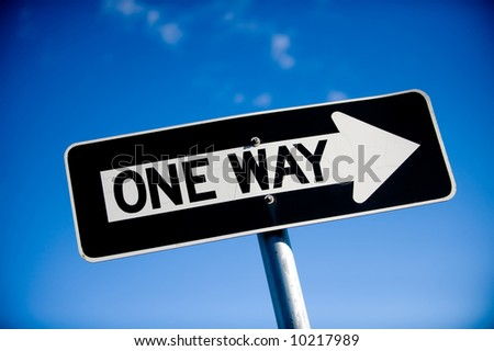 Image of a slightly angled one way sign against blue sky - stock photo
