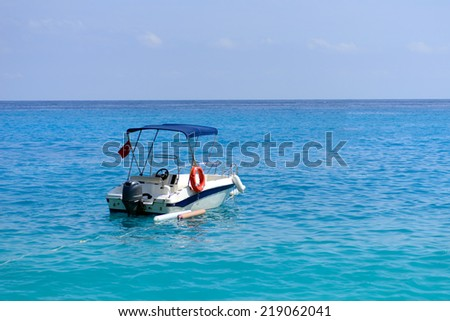 Image of a small boat in the sea at Olu Deniz, a small rsort on the turquoise coast of south-western turkey, frequently voted by travellers and tourism journals as 1 of the top beaches in the world  - stock photo