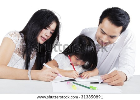 Image of a smart little girl learns to write on the book with her father and mother, isolated on white background