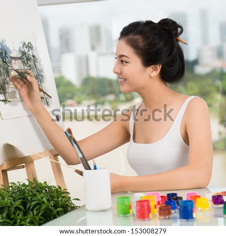 Image of a smiling artist drawing his picture in the studio - stock photo
