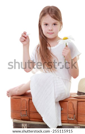 Image of a smiling little girl in a summer dress sitting on old suitcase for traveling on a white background on Beauty and Fashion - stock photo